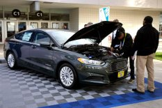 Workers prepare a 2015 Ford Fusion hybrid car for display at the International Consumer Electronics show in Las Vegas