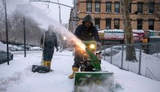 A man plows a sidewalk after a snow storm in the Brooklyn borough of New York